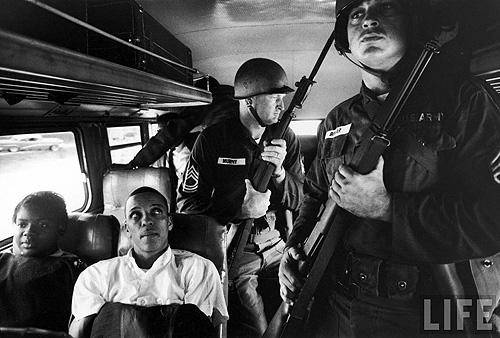 Freedom Riders Julia Aaron & David Dennis sitting on board interstate bus as they and 25 others are escorted by 2 National Guardsmen holding bayonets, on way from Montgomery, AL to Jackson, MS, May, 1961 - Photo by Paul Schutzer<br/>
