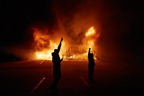 Onlookers stand on West Florissant Avenue as an AutoZone burns early Tuesday, Nov. 25, 2014 in Dellwood, Mo. A grand jury decided not to charge Ferguson police officer Darren Wilson in the fatal shooting of Michael Brown.<br/>