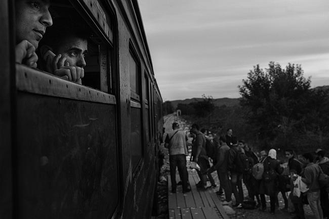 Rwand Ali, from Syria, watches refugees board a train to the Serbian border, 2015 Archival Pigment Print
