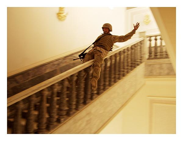 A marine slides down the marble handrail in Saddam's palace in Tikrit Archival Pigment Print