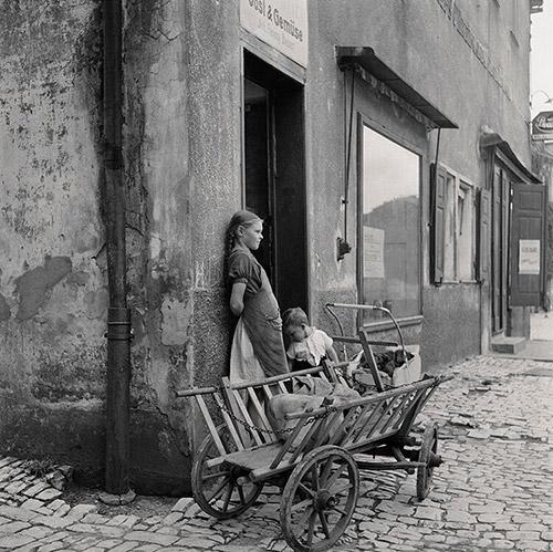 Waiting For Mom. Two children wait outside a grocery store with the family shopping cart, Hoescht, Germany, 1946.  Archival Pigment Print