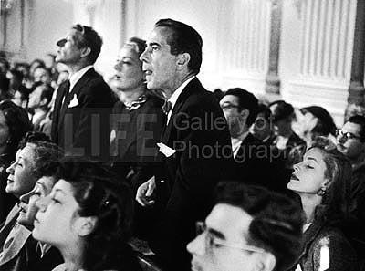 Actors Danny Kaye, June Havoc and Humphrey Bogart, with wife, actress Lauren Bacall sitting beside him, listening intently a hearing regarding communists in the film industry, 1947 Gelatin Silver print