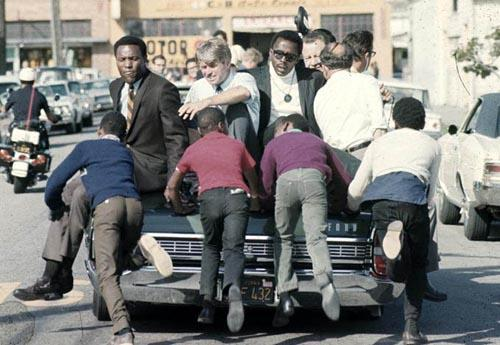 The Kennedy campaign travels through the Watts section of Los Angeles on the last day before the primary, 1968<br/>